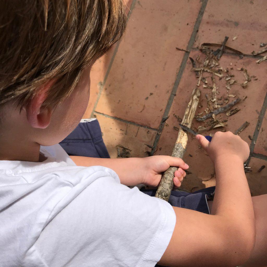 Kind snijdt stok voor broodjes bakken